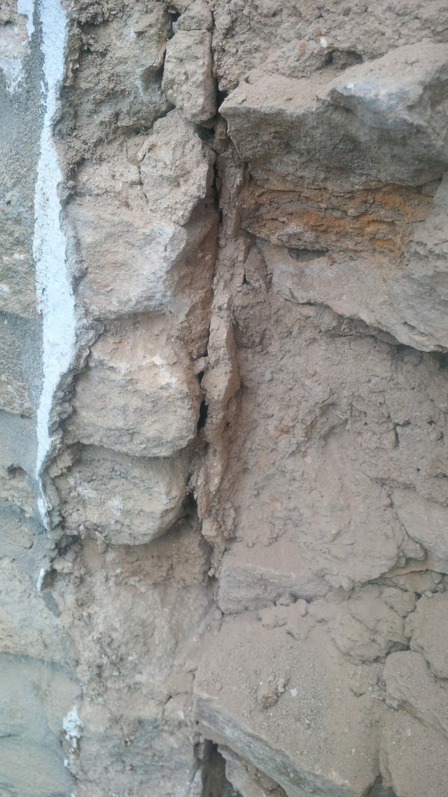 left hand flank showing traces of old lime render trapped by the later masonry (on the left with some painted cement render still attached, the old masonry on the right, old render or plaster in the centre